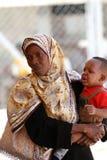 Африканские мусульманские женщины, большой шарф цвета, держа младенца ее оружия. Стоковое фото RF