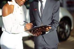 Африканские пары получая ключ автомобиля от торговца в выставочном зале и подписывая контракт Стоковое Изображение