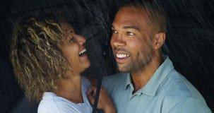 Африканские пары смеясь над под зонтиком совместно Стоковое Изображение RF