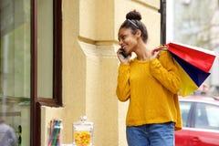 Африканские покупки женщины и говорить на мобильном телефоне Стоковое фото RF