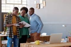 Африканские предприниматели говоря совместно над обработкой документов в современном офисе Стоковые Изображения RF