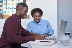 Африканские предприниматели дела работая на компьтер-книжке в белом офисе Стоковые Изображения RF