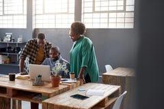 Африканские предприниматели используя компьтер-книжку совместно в современном офисе Стоковая Фотография RF