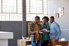 Африканские предприниматели обсуждая обработку документов совместно в современном офисе Стоковые Изображения RF