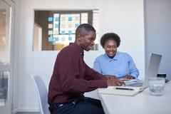 Африканские предприниматели работая на компьтер-книжке в современном офисе Стоковое Изображение