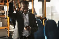 Африканские тексты чтения бизнесмена и нося наушники на шине стоковое фото rf