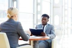Африканский бизнесмен говоря к белокурой женщине в встрече Стоковое фото RF