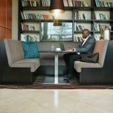 Африканский бизнесмен работая на компьтер-книжке на кафе Стоковое Изображение RF