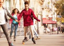 Африканский девочка-подросток rollerblading на бортовой прогулке Стоковые Фотографии RF