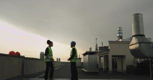 Африканский инженер женщины и ее партнер на даме строительной площадки делают предложение для его партнера на крыше  видеоматериал