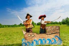 Африканский мальчик, девушка в костюмах пиратов с шпагами Стоковые Фото