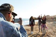 Африканский молодой человек фотографируя друзей телефоном Стоковое Изображение