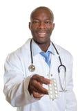 Африканский доктор показывая пилюльки стоковое фото rf