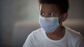 Африканский ребенк в белой рубашке нося защитную маску, стационарный больного, медицину стоковые изображения