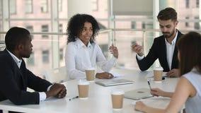 Африканский руководитель работника обсуждая проект с коллегами на групповой встрече акции видеоматериалы