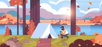 Африканский турист hiker человека устанавливая шатер подготавливая для располагаясь лагерем реки природы ландшафта осени восхода  иллюстрация штока