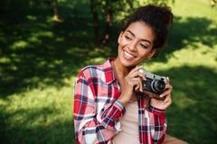 Африканский фотограф женщины сидя outdoors в парке Стоковое Изображение RF