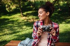 Африканский фотограф женщины сидя outdoors в парке Стоковые Изображения