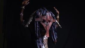 Африканский человек в ритуальных одеждах и орнаментах танцуя на черной предпосылке, замедленном движении акции видеоматериалы