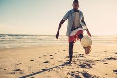 Африканский человек играя с футбольным мячом на пляже Стоковые Фотографии RF
