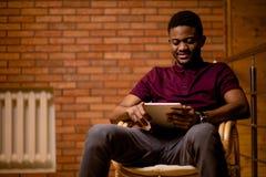 Африканский человек используя таблетку для видео- переговора пока ослабляющ на кресле Стоковое фото RF