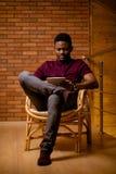 Африканский человек используя таблетку для видео- переговора пока ослабляющ на кресле Стоковая Фотография RF
