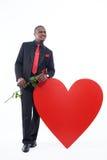 Африканский человек в черной сюите держа красную розу Стоковое фото RF