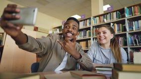 Африканский merican парень и кавказская девушка имеют потеху усмехаясь и принимая фото selfie на камере smartphone на университет видеоматериал