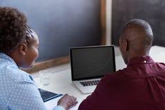 2 африканских коллеги используя компьтер-книжку совместно в офисе Стоковая Фотография RF