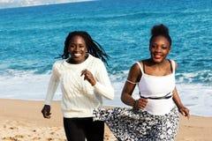 2 африканских предназначенных для подростков девушки бежать на пляже Стоковые Изображения