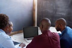 3 африканских сотрудника используя компьтер-книжку совместно в офисе Стоковые Изображения