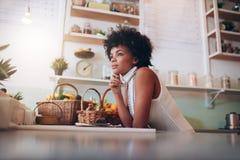 Африканское женское предприниматель бара сока смотря отсутствующий и думать стоковые изображения rf