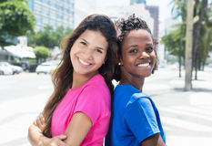 2 африканское и кавказские женщины смотря камеру в городе Стоковое Изображение RF