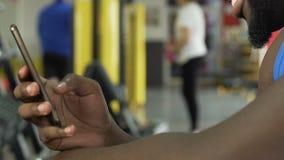 Афроамериканец используя мобильный телефон в спортзале, усмехаясь, сообщении с друзьями акции видеоматериалы