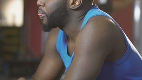 Афроамериканец обтирая его сторону с полотенцем в спортзале, вымотанном после тренировки сток-видео