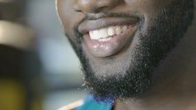 Афроамериканец поворачивая вверх по его стороне к камере, давая красивую широкую улыбку видеоматериал