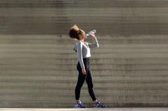 Афроамериканец резвится женщина выпивая от бутылки с водой Стоковые Фото