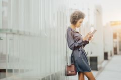 Афро-американская близко девушка рядом с стеной с цифровой таблеткой стоковое изображение