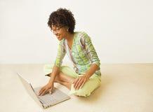 Афро-Американская вскользь женщина на компьтер-книжке стоковые изображения rf