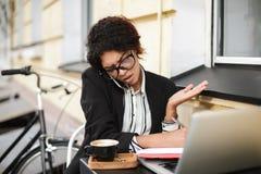 Афро-американская девушка в стеклах сидя на таблице и эмоционально говоря на ее мобильном телефоне Дама с темное курчавым Стоковые Изображения