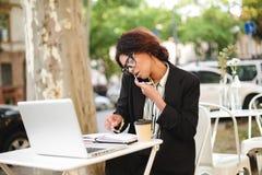 Афро-американская девушка в стеклах сидя на таблице кафа и говоря на ее мобильном телефоне пока работающ повелительница довольно Стоковое фото RF