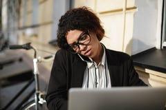Афро-американская девушка в стеклах сидя на таблице кафа и работая на ее компьтер-книжке Дама с темным вьющиеся волосы внутри стоковые изображения