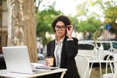 Афро-американская девушка в стеклах сидя на таблице кафа с чашкой кофе в руке и компьтер-книжке на таблице Портрет Стоковые Изображения