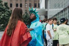 Афро-американская девушка одетая как статуя свободы говоря с ее другом в Нью-Йорке, США стоковые изображения rf