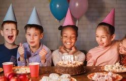 Афро-американская девушка празднуя день рождения и делая желание стоковые фото