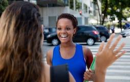 Афро-американская девушка битника встречает кавказскую женщину внешнюю в городе Стоковое Изображение