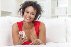 Афро-американская девушка слушая к наушникам mp3 плэйер Стоковые Фотографии RF