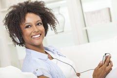 Афро-американская девушка слушая к наушникам mp3 плэйер Стоковая Фотография RF