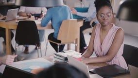 Афро-американская женская коммерсантка при smartphone сидя таблицей офиса в занятом современном coworking замедленном движении акции видеоматериалы