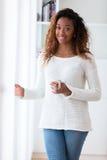 Афро-американская женщина в ее живущей комнате выпивая держащ cof стоковое изображение rf